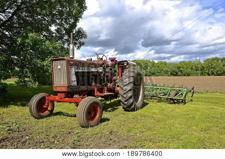 OSAKIS, MINNESOTA, May 26, 2017: The old 706 Farmall tractor pulling a field cultivator was a model name and later a brand name for tractors manufactured by the American company International Harvester IH