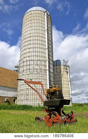 An oily tiller  machine for digging a garden is left near a barn with two tall silos.