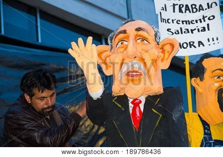 Quito, Ecuador - December 31, 2016: An unidentified man with a traditional monigotes of Paco Moncayo representing political figure, with a short description that will get burned to celebrate new year in Ecuador.