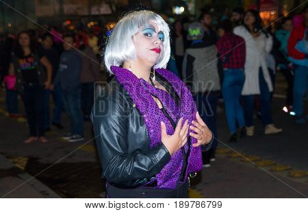 Quito, Ecuador - December 31, 2016: An unidentified woman wear dark clothes to represent a widowed woman, they usually make a silly moves or dances and ask for money to the people walk around to celebrate new year in Ecuador.