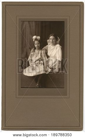 UNITED STATES - CIRCA 1910: Paper framed portrait of two sisters clothed in their best dresses and jewelry