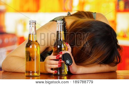 Portrait of a drunk woman sleeping over a wooden table and holding an open beer and car keys with her hand, in bar background.