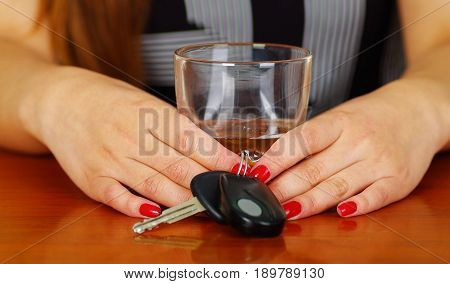 Close up of a woman holding with both hands a glass of whiskey and car keys, over a wooden table.