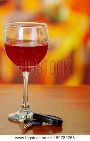 Close up of a cup of red wine with car keys on wooden table.