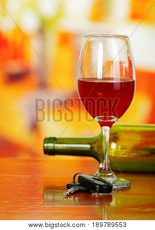 Close up of a cup of red wine with car keys on wooden tablea with a blurred green botle of wine behind.