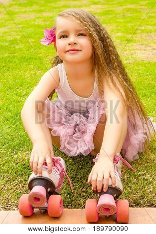 Little girl preschool beginner sitting in the grass with her roller skates, in a grass background.