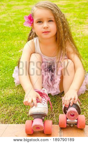 Little girl preschool beginner touching her roller skates, in a grass background.