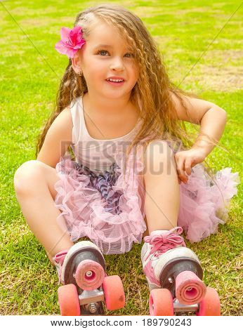Little girl preschool beginner in roller skates, in a grass background.