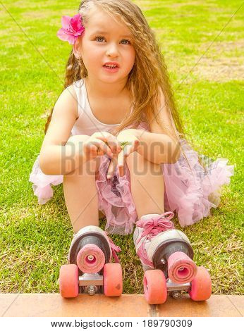 Little girl preschool beginner in roller skates, putting some grass in her hand and watching at camera, grass background.