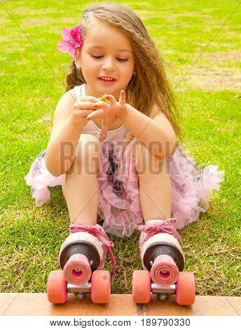 Little girl preschool beginner in roller skates, putting some grass in her hand, grass background.