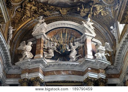 ROME, ITALY - SEPTEMBER 02: Angels holding a globe with golden rays, and initials IMAS for the names Jesus and Maria, main altar in church Gesu e Maria in Rome, Italy on September 02, 2016.