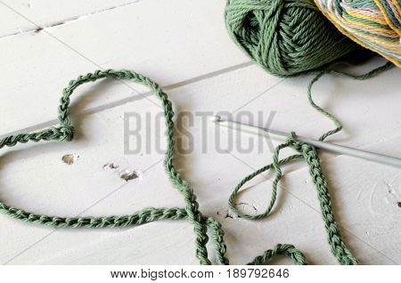 A close up image of a green crochet heart symbol and crochet yarn.