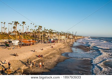 OCEANSIDE, CALIFORNIA - MARCH 23, 2017:  People enjoy an evening of leisure activities at the popular Southern California beach.