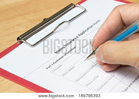 Mand fill the home insurance application form with red file on wooden table