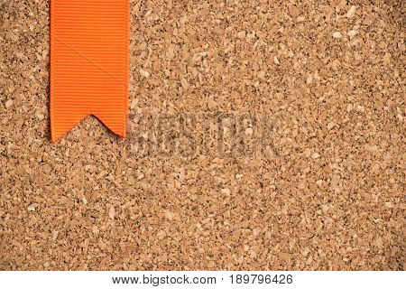 Orange ribbon on cork board texture background