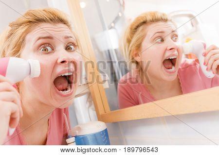 Shocked Woman Using Facial Cleansing Brush