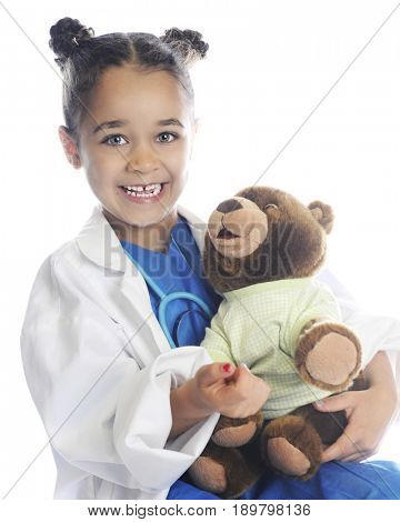 A happy elementary girl pretending to be a health care provider taking care of a patient's teddy bear.  On a white background.