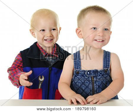 Two adorable toddlers standing together at their work table. One wears a plaid flannel shirt and tool vest, the other is in overalls with no shirt. Focus is on boy on the left.