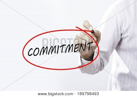 Businessman Hand Writing commitment with a marker over transparent board Business concept.