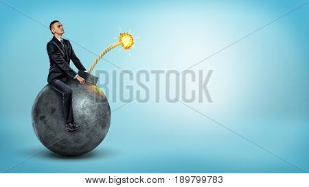 A small businessman riding a big round bomb with a lit fuse on blue background. Work under pressure. Strict deadline. Dangers of tardiness.