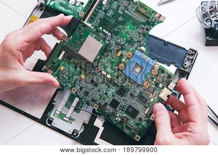 Diagnostics, repair, laptop service concept. Motherboard from the computer, pc in the repair shop top view