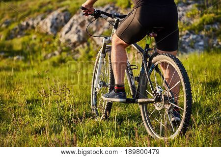 Close-up of detail of cyclist man feet riding mountain bike on rocky trail. Sportsman in the black shorts and with sportive shoes. Detail of the bike. Horizontal photo. Concept of the healthy and active lifestyle.