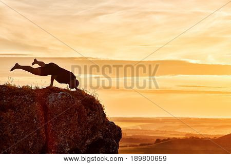 Silhouette of man doing yoga meditation against beautiful sky with clouds. Horizontal photo of young sportsman and beautiful lnadscape with sunset. Practicing yoga in the countryside. Concept of the healthy and active lifestyle.