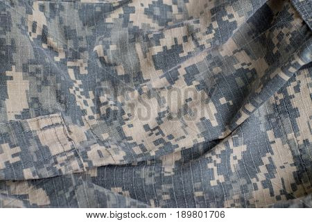Camouflage fabric texture. A piece of army clothes. Camouflage background.