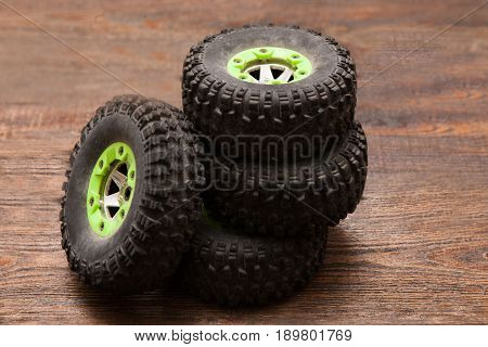 Wheels of Rc radio control car crawler model toy. Pile of spare parts for suv in repairshop workplace, top view