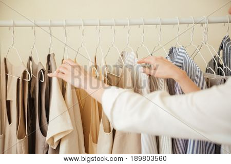 Close up of woman hands choosing clothes hanging on rack in workshop