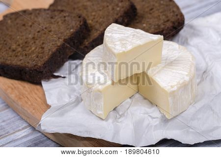 Brie type of cheese. Camembert cheese. Fresh Brie cheese and a slice on a wooden board with black bread slice. Italian French cheese. Close up