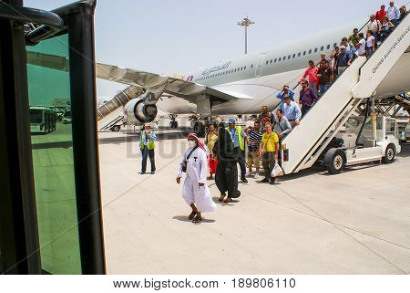 Qatar. May 2009. Passengers disembark from the aircraft Qatar Airways at the airport of Doha. In the foreground a woman in a niqab and a man in Muslim clothes