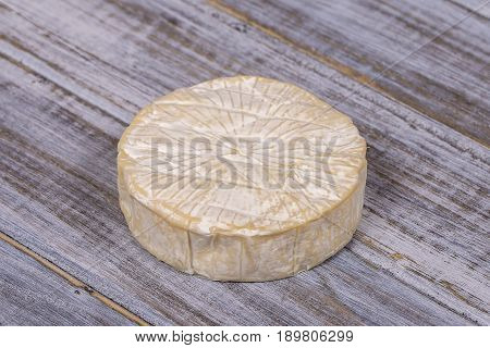 Brie type of cheese. Camembert cheese. Fresh Brie cheese on a wooden board. Italian French cheese. Close up