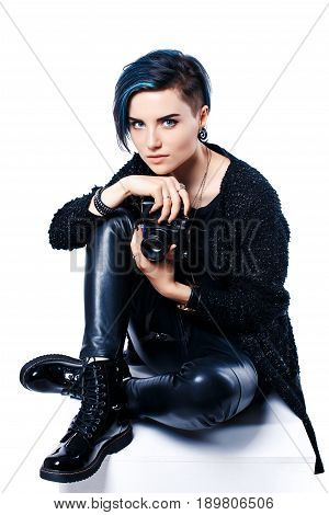 Portrait of stylish young girl with blue hair sitting on floor with camera in hands and looking at camera.Isolated