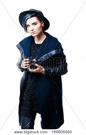 Portrait of serious beautiful girl in hat with camera in hands looking at camera.Isolated