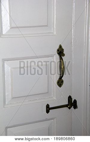 Vertical image of painted white door in home, with black hardware