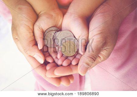 parent holding child hands with Australian money