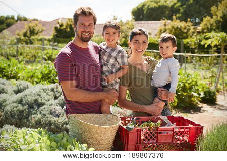 Portrait Of Family Working On Community Allotment Together