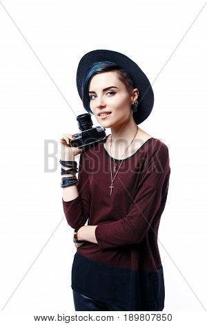 Portrait of beautiful young girl in hat with vintage camera in hand.Studio shot