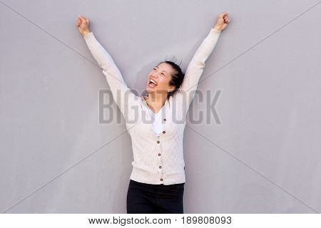 Laughing Woman With Arms Raised Against Gray Background