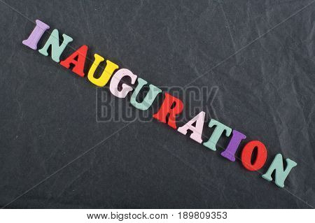 Iinauguration . English word on black board background composed from colorful abc alphabet block wooden letters, copy space for ad text. Learning english concept