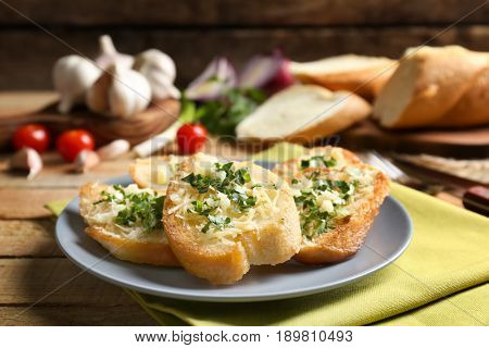 Tasty bread slices with grated cheese, garlic and herbs on plate