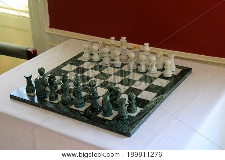 Bright and colorful marble chess board and pieces set on corner table in room of home.