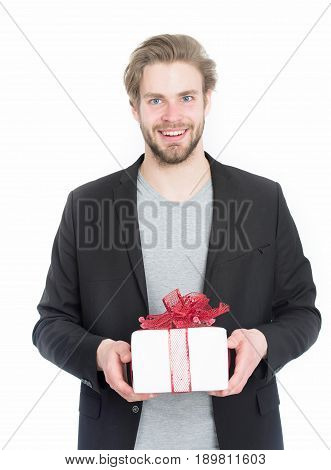handsome bearded guy happy businessman or sexy smiling man with beard and stylish hair with present box in red ribbon bow in black formal jacket isolated on white background