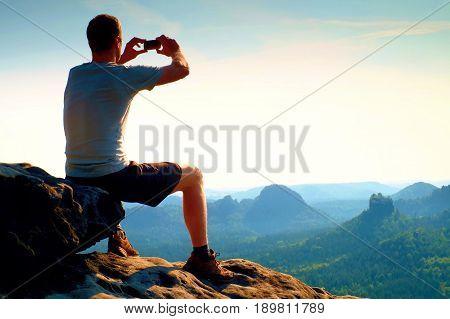 Sitting Hiker Is Taking Photo By Smart Phone On Sharp Cliff Of Mountain At Sunrise.