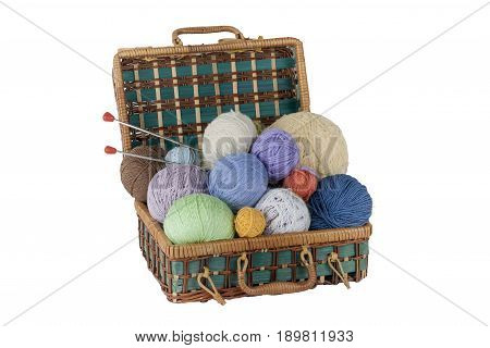 Ball of wool, needles and woolen sweater with spokes for handmade knitting in basket on wooden table