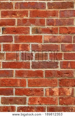 Vertical image of old, weathered brick wall showcases the craftsmanship in masonry.