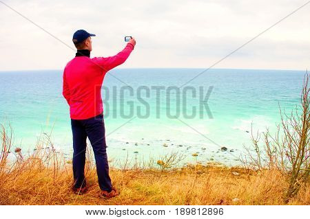 Tourist In Baseball Cap And Pink Windcheater Takes Photo By Cellular Phone. Windy Day At Ocean