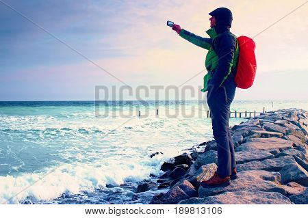 Hiker On Pier Photograph Morning Sea. Tourist With Smart Phone In Hand, Backpack In Red Raincoat. Fa