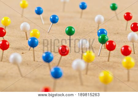 Group of thumbtacks pinned on corkboard .
